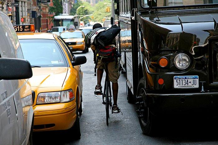 Man on a bike between two cars in new york city